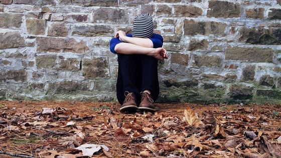Человек в депрессии сидит на листве