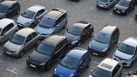Автомобили стоят в несколько рядов на парковке