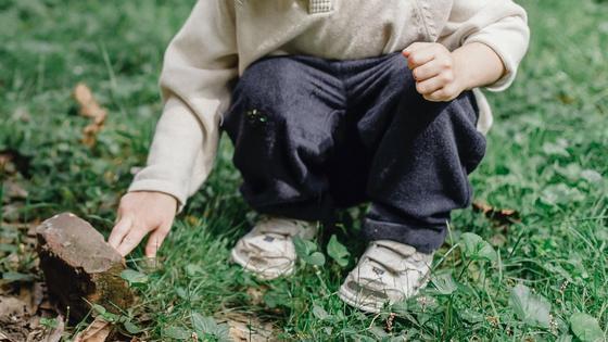 Ребенок сидит на лужайке