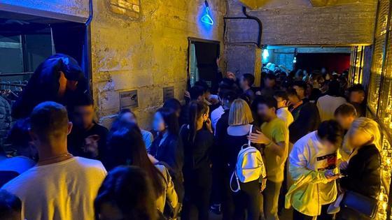 Толпа людей стоит в коридоре ночного клуба
