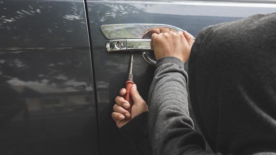 Человек взламывает дверь авто отверткой