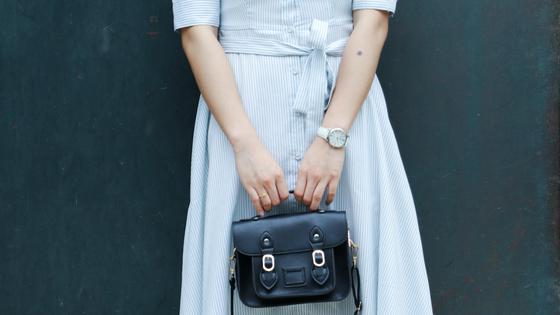 Девушка в голубом платье с черной сумкой в руках
