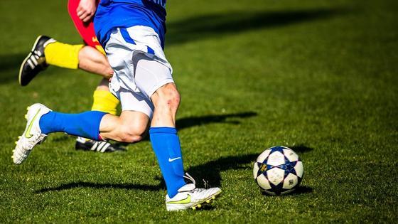 Футболисты на поле передают друг другу мяч