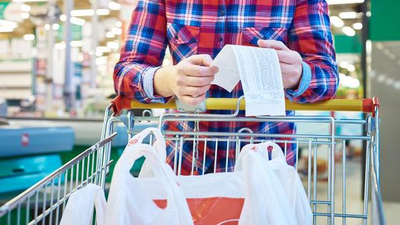 Женщина смотрит в чек в магазине