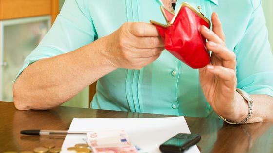 Пенсионерка заглядывает в свой кошелек