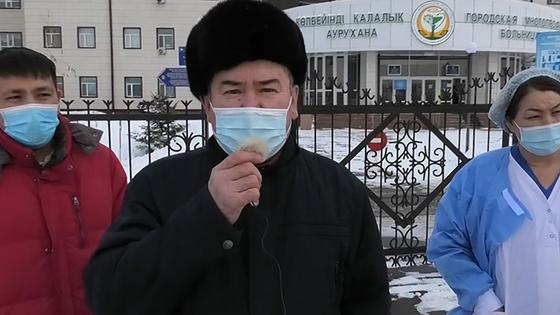 Трое человек в масках стоят перед зданием больницы