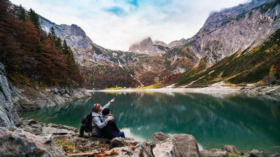 Пара молодых людей сидит на фоне гор