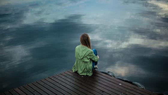 Девушка сидит на пирсе у водоема