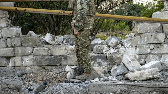 Военный стоит у разрушенной стены