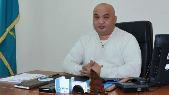 Бахытжан Алибеков сидит за столом