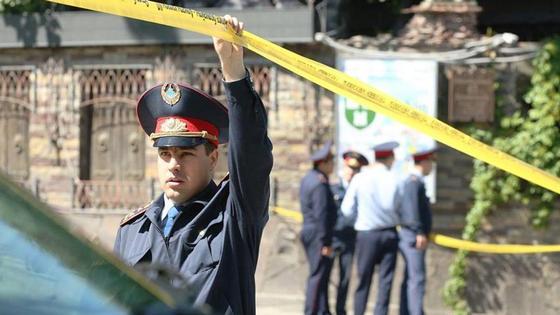 полицейский держит ленту рядом с местом преступления