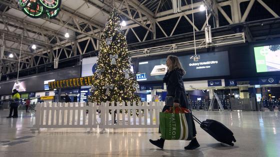 Женщина идет по вокзалу с багажом