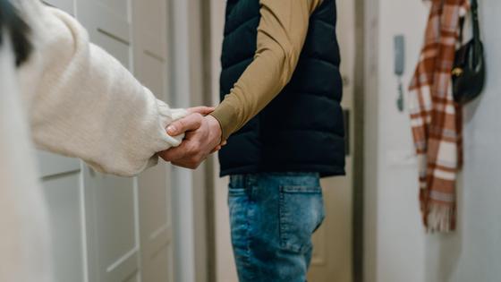 Пара держится за руки на прощание