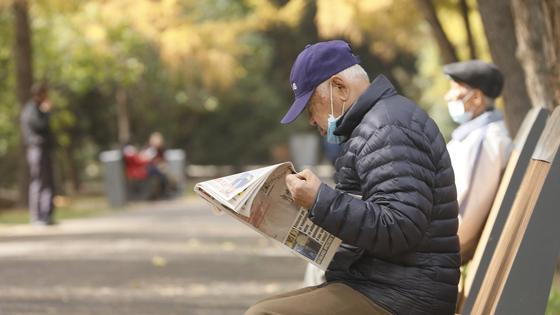 Мужчина читает газету, сидя на скамейке