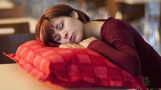Девушка спит на подушке за столом