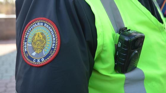 Полицейский в форме стоит на дороге