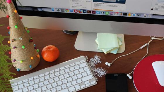 Маленькая елочка, клавиатура, мандарин, смартфон на рабочем столе