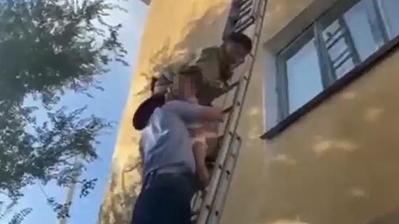 Спасатель передает ребенка полицейскому на лестнице