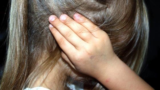 Девочка закрывает уши руками