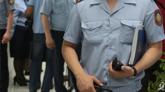 полицейский держит в руках рации