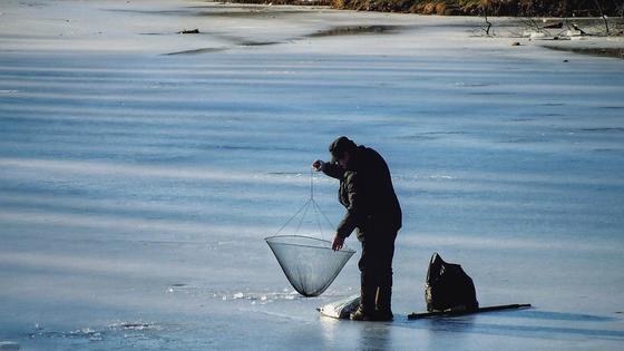 Рыбак ловит рыбу в проруби
