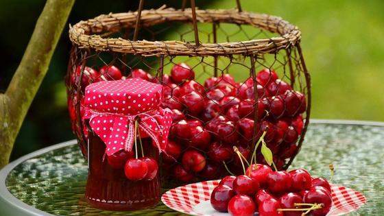 Банка с черешневым вареньем, корзинка и тарелка со свежими ягодами