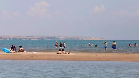 Люди отдыхают у берега на Капшагайском водохранилище
