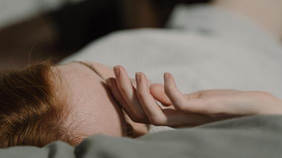 Девушка лежит на кровати и прикрывает лицо руками