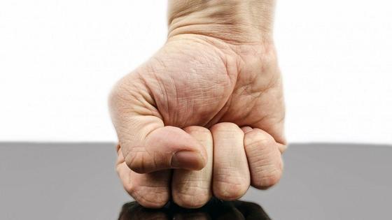 Мужской кулак ударяет об стол