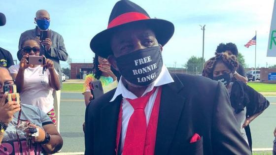 Темнокожий мужчина в черной шляпе и маске в красном галстуке