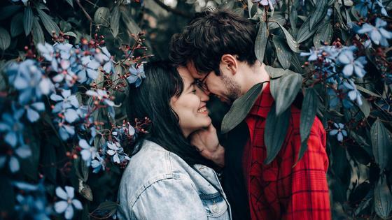 Парень и девушка стоят, прижавшись друг к другу, на фоне цветущих деревьев
