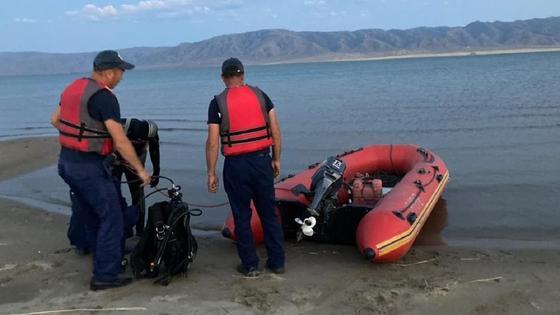 Спасатели стоят на берегу водоема