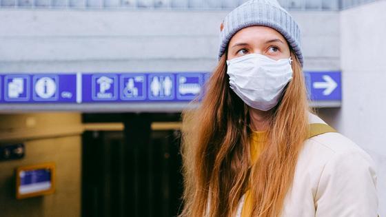 Девушка в маске стоит в аэропорту