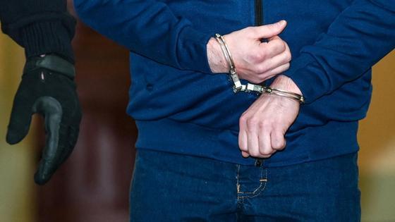 Мужчина в наручниках идет по коридору