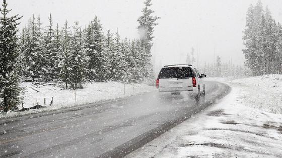Автомобиль несется по заснеженной трассе