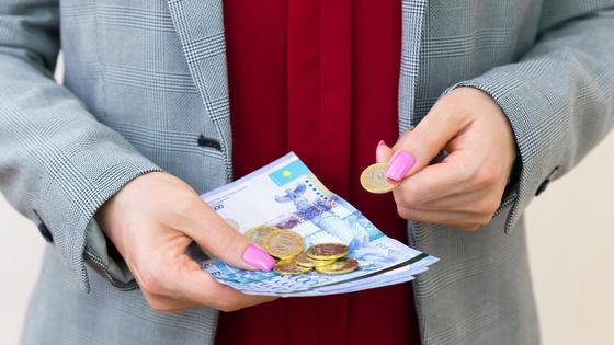 Женщина держит в руках купюры и монеты тенге