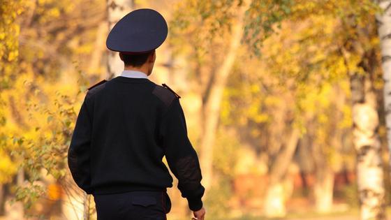 Полицейский идет по улице осенью