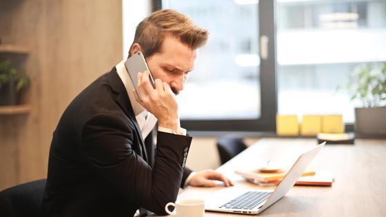 Мужчина с телефоном сидит за столом