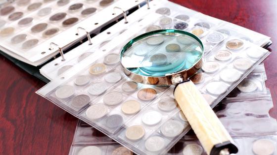 Лупа лежит на упакованной коллекции монет