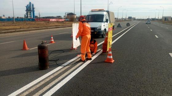 Рабочие наносят на дорогу новую сплошную линию