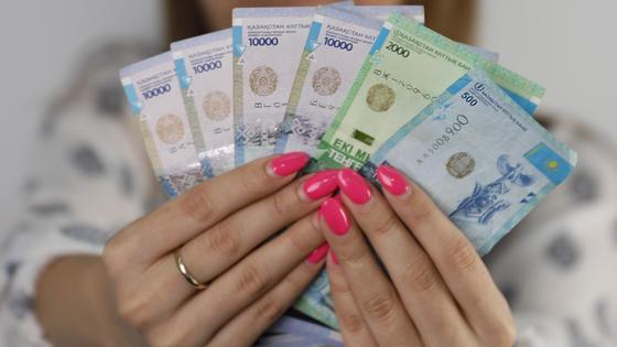 девушка держит в руках 42,5 тыс. тенге