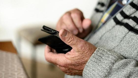 Пожилой мужчина держит в руке телефон