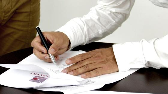 Мужчина оставляет подпись в документе