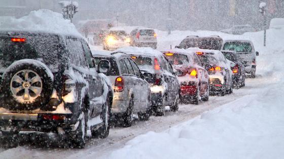 Машины едут по дороге в снегопад