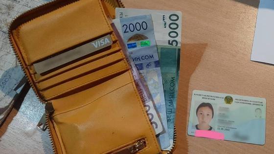 Кошелек с деньгами и удостоверение личности лежат на столе
