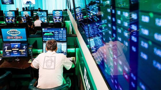 Человек сидит за компьютером в букмекерской конторе