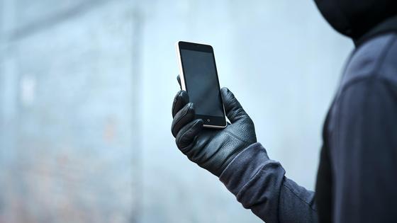 Мужчина в черной одежде и в перчатках держит в руке смартфон