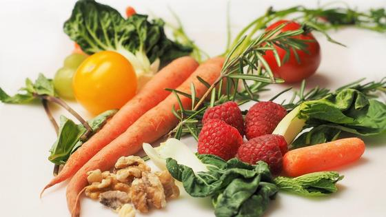 Морковь, помидоры, малина, орехи, зелень лежат на столе