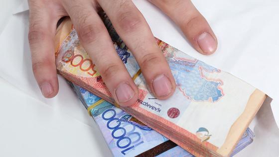 Рука лежит на конверте с деньгами