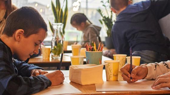 Дети в столовой едят и рисуют